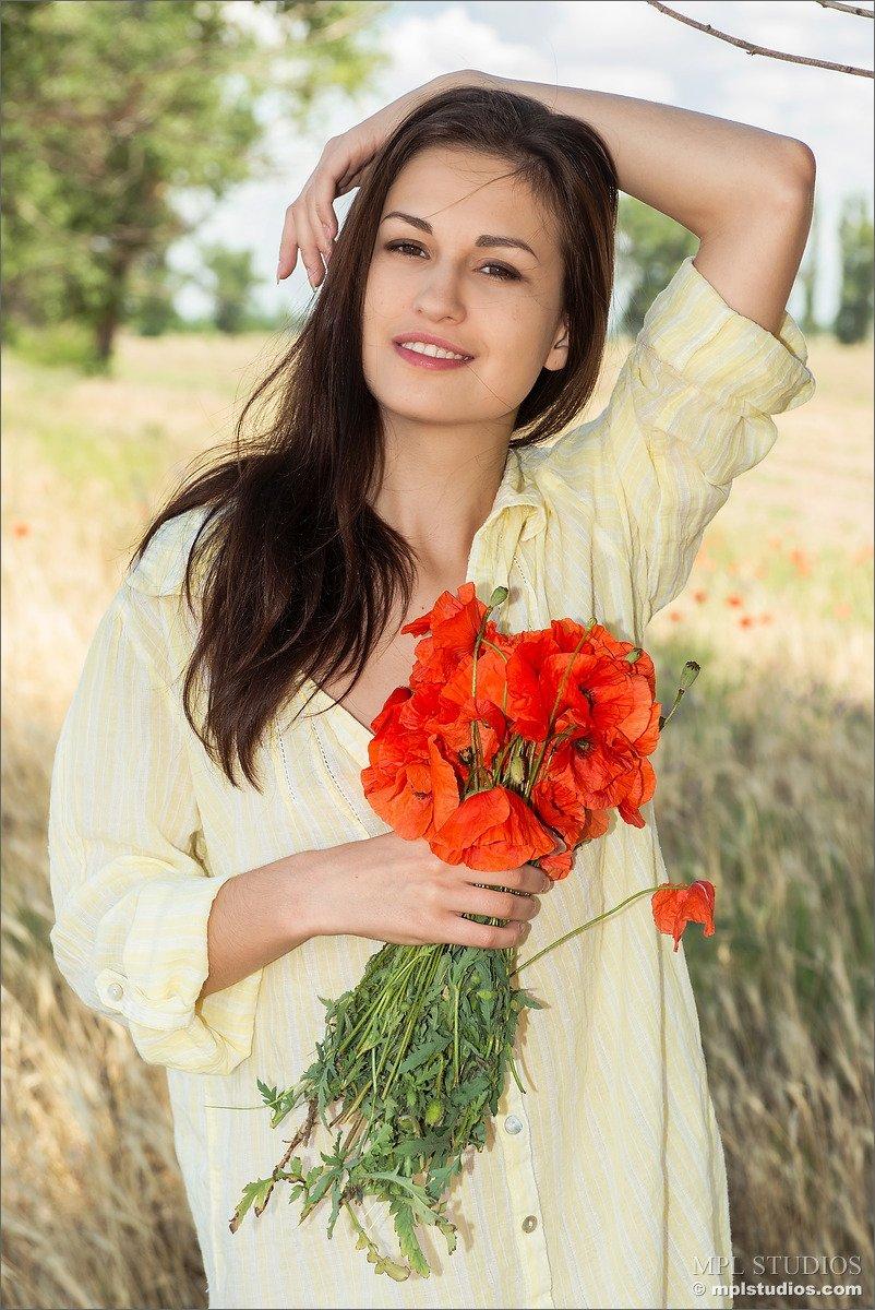 Голая девушка в поле собирает цветы