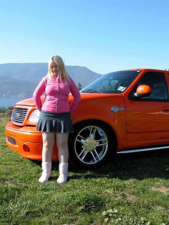 Низкорослая блондинка с пухлыми ножками показывает сиськи и поднимает юбку
